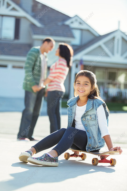 Smiling girl on skateboard in driveway
