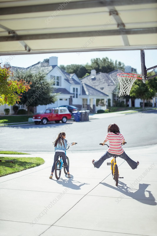 Girls riding bicycles in sunny driveway