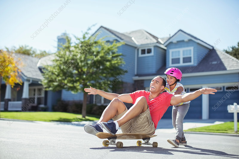 Daughter pushing father on skateboard