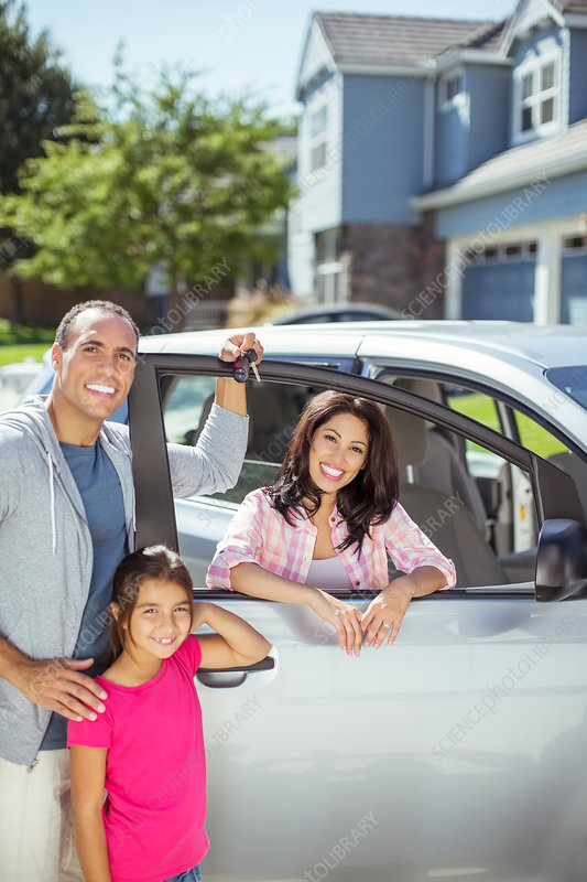 Smiling family at car in driveway