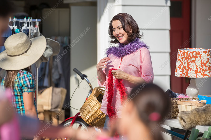 Woman trying on feather boa at yard sale