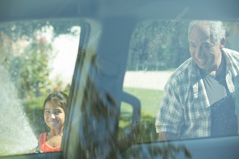 Grandfather and granddaughter outside car