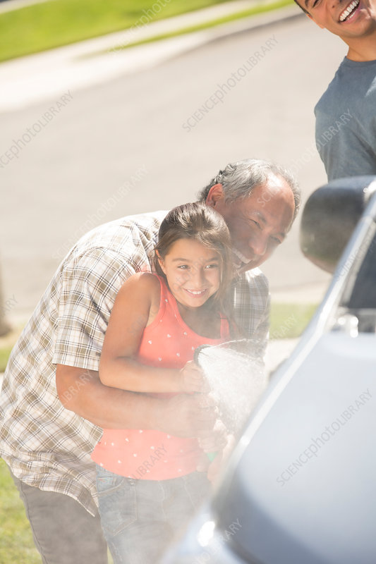 Grandfather and granddaughter washing car