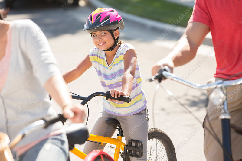Smiling girl riding bicycle with parents