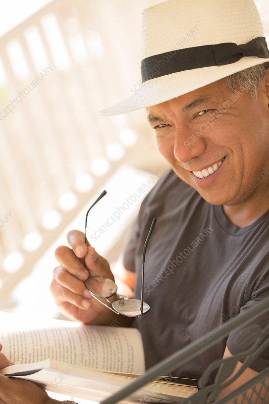 Portrait of smiling man reading book