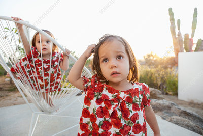 Twin baby girls playing on patio