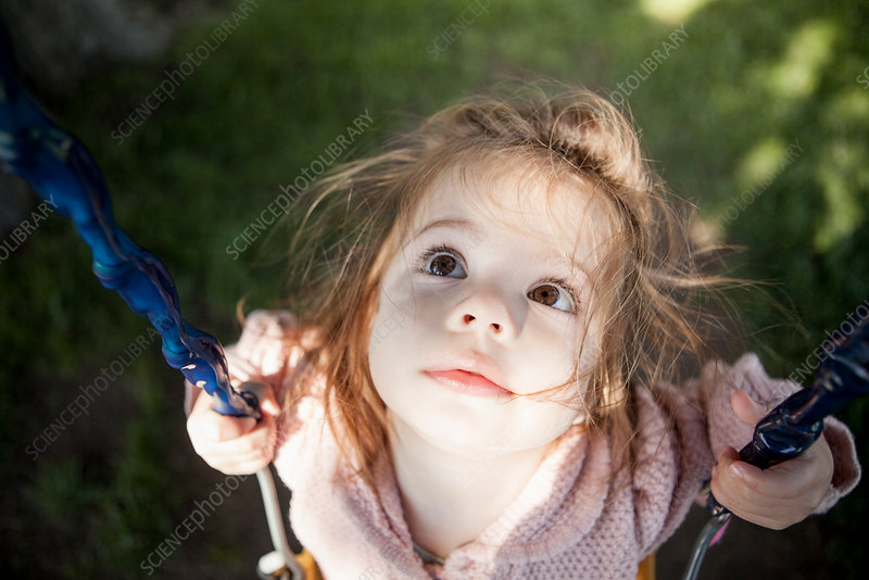 Baby girl sitting on swing outdoors