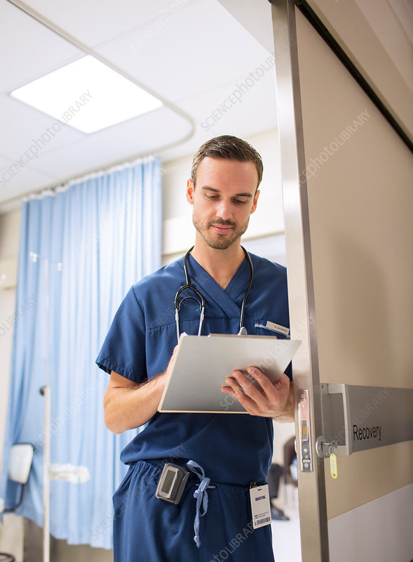 Male doctor taking notes on clip board