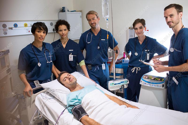 Doctors standing around smiling patient