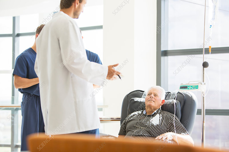 Two doctors talking to senior patient