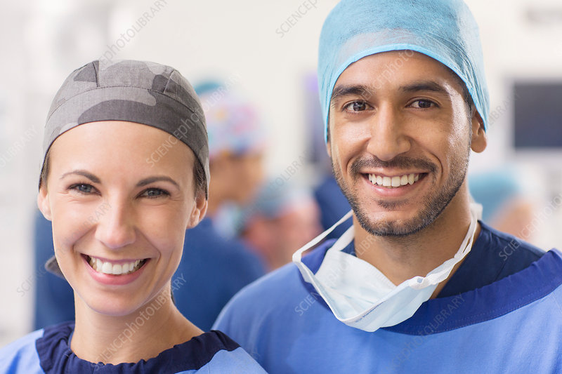 Smiling doctors wearing surgical caps