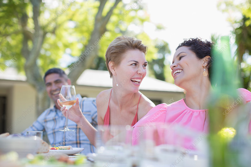 Women talking at table outdoors