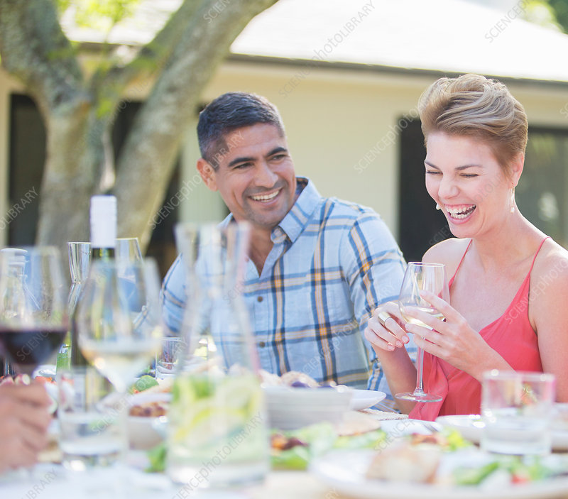 Couple laughing at table outdoors