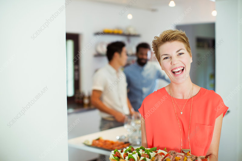 Woman carrying tray of food at party