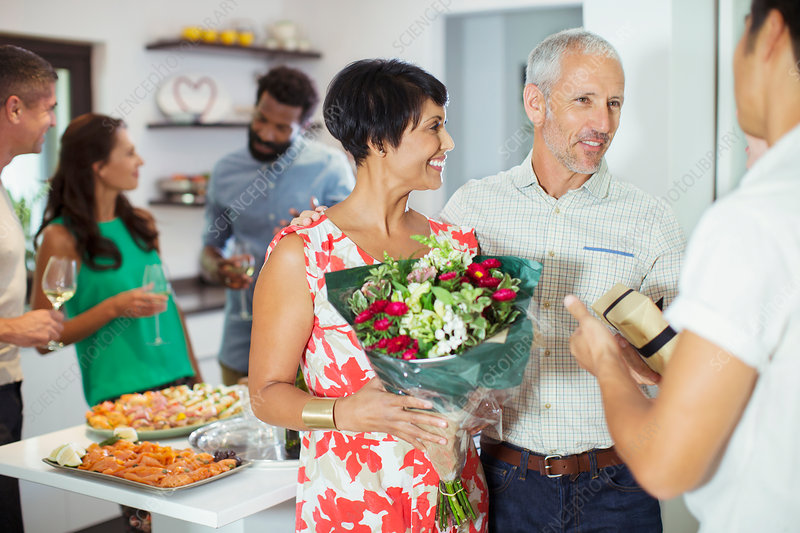 Couple bringing flowers to party