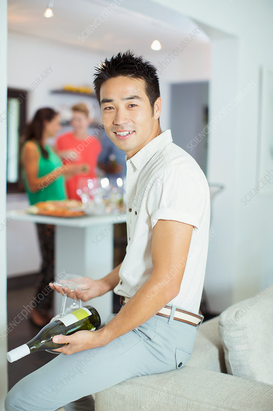 Man holding bottle of wine at party