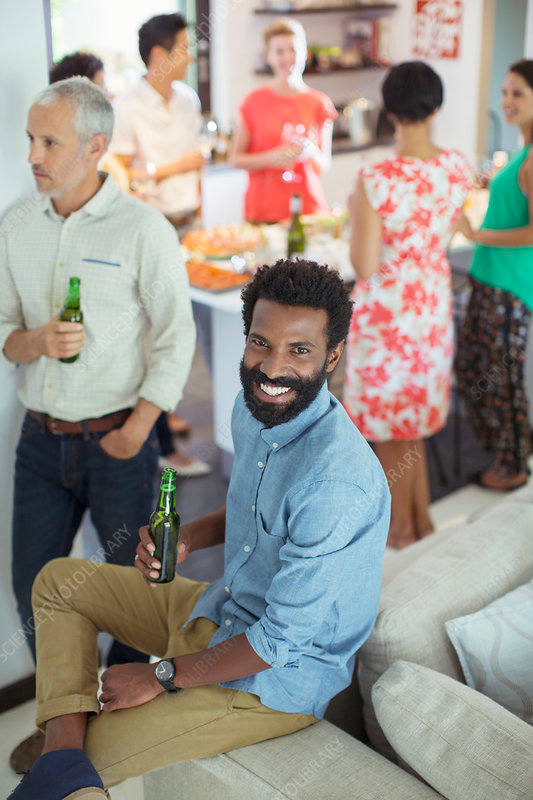 Man smiling on sofa at party