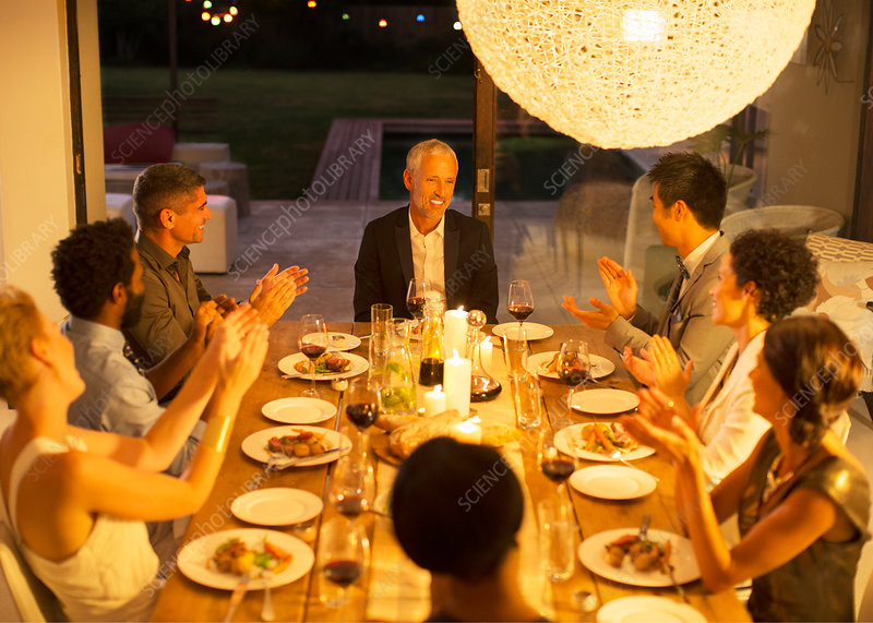 Friends applauding man at dinner party