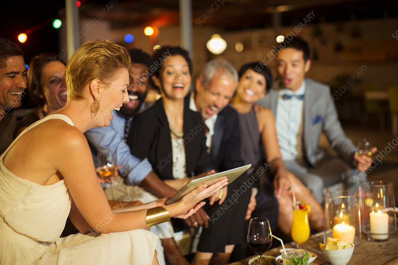 Friends using digital tablet at party