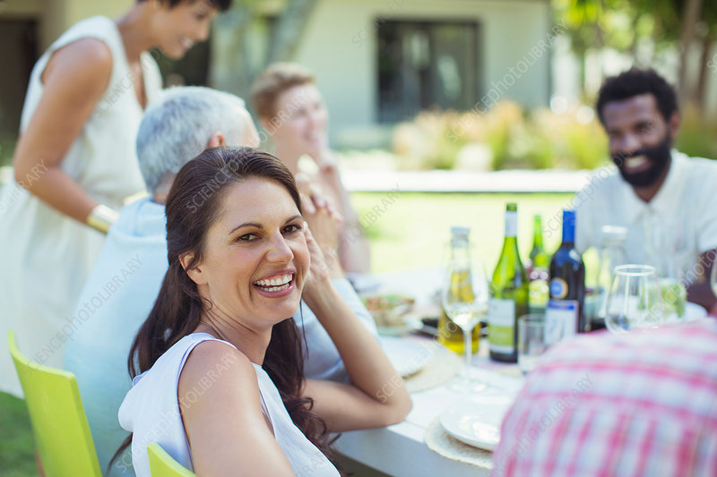 Woman smiling at table outdoors