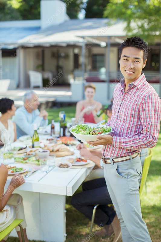 Man serving friends at table outdoors