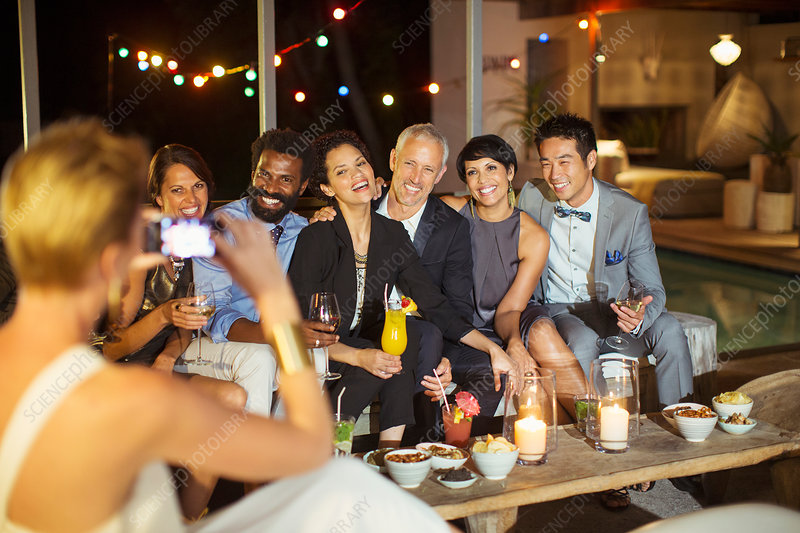 Woman taking picture of friends at party
