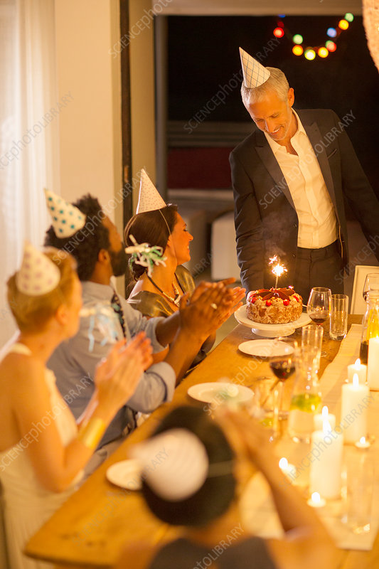 Man serving birthday cake at party