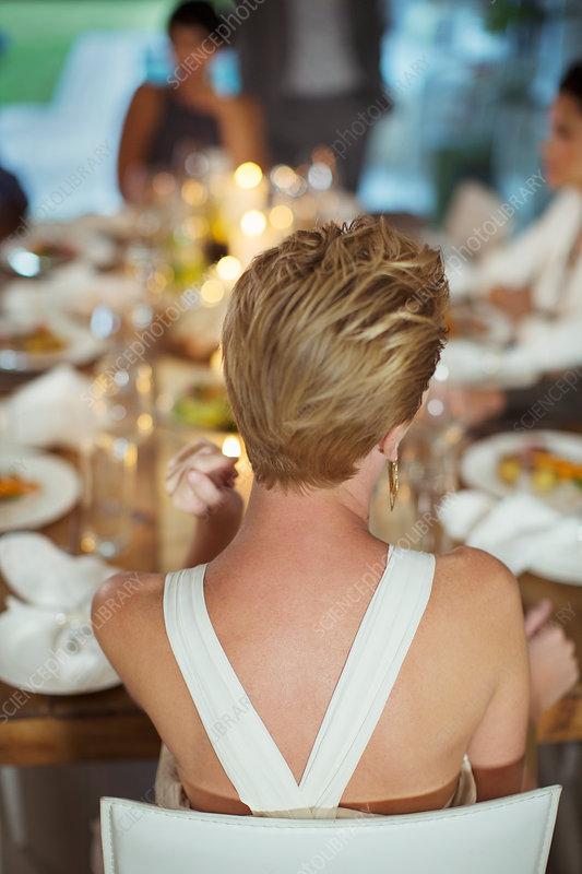 Woman sitting at dinner party
