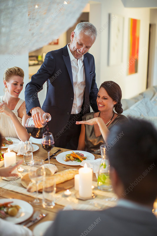 Man serving wine at dinner party