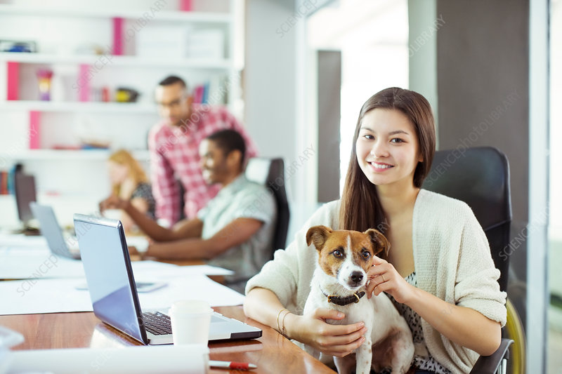 Woman petting dog in office