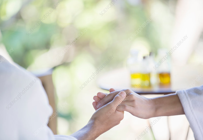 Couple in bathrobes holding hands in spa