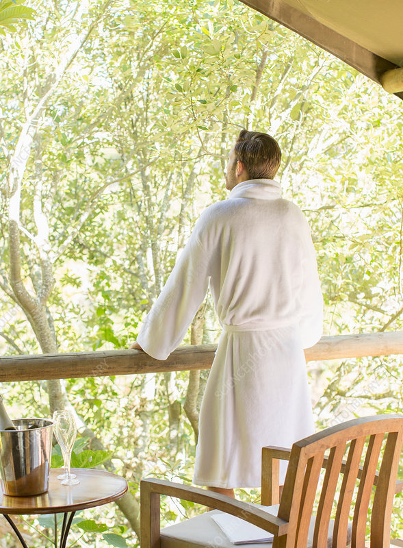 Man wearing bathrobe on balcony