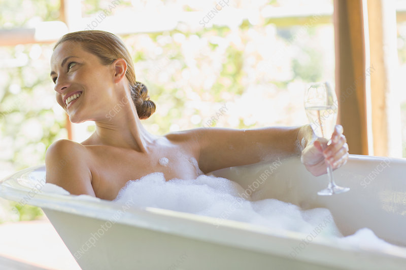 Woman having champagne in bubble bath
