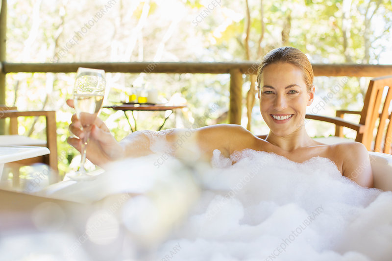 Woman drinking champagne in bubble bath