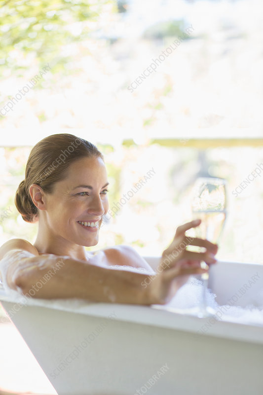 Woman drinking champagne in bathtub