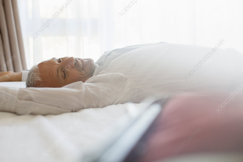 Businessman laying on bed in hotel room