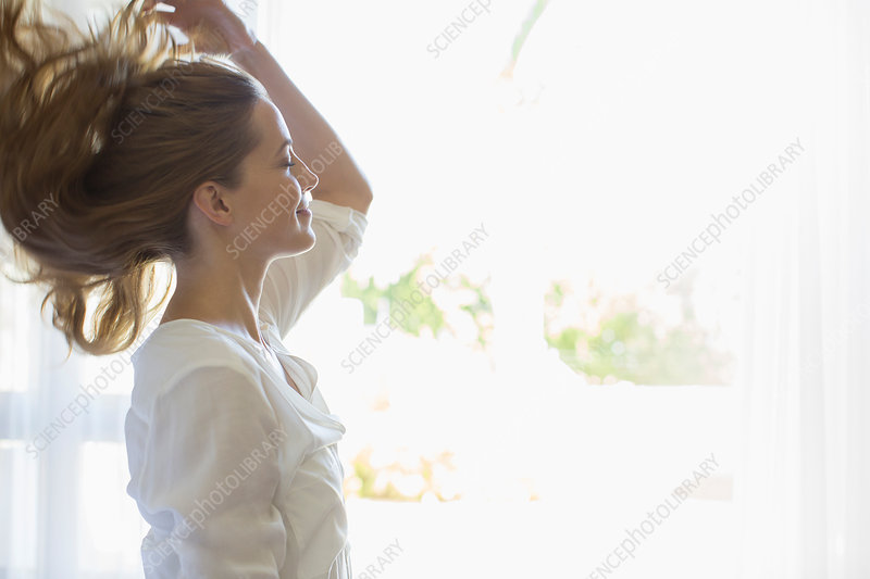 Woman tossing her hair indoors