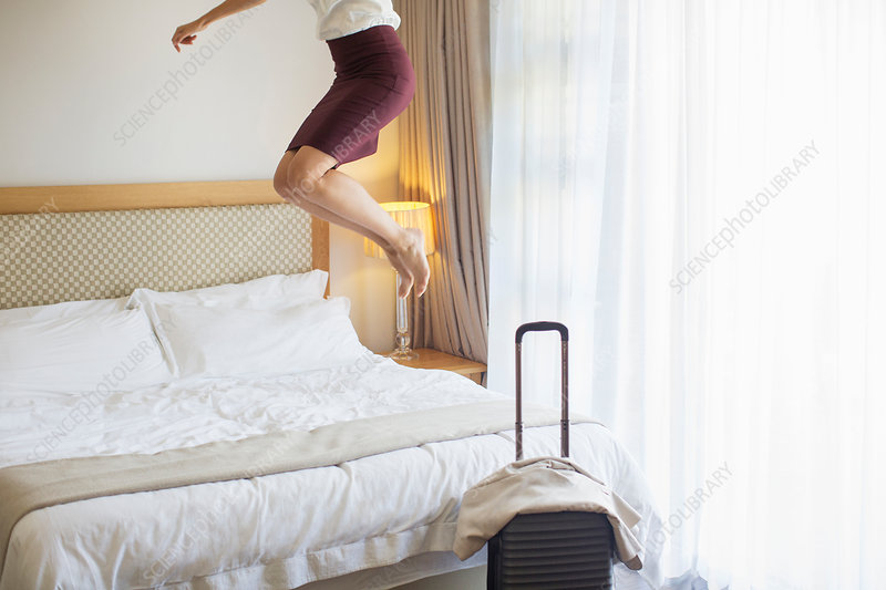 Businesswoman jumping on bed