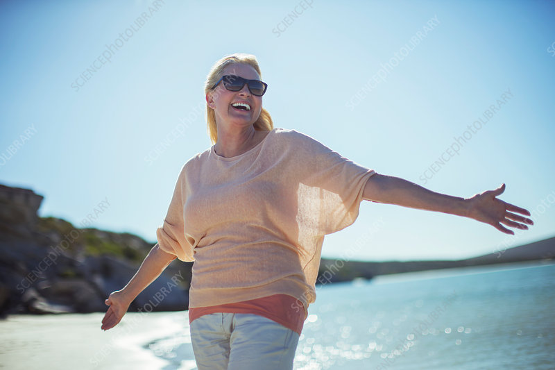 Older woman smiling in sun on beach