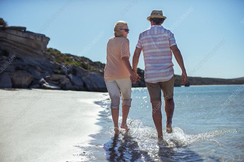 Couple holding hands walking along shore