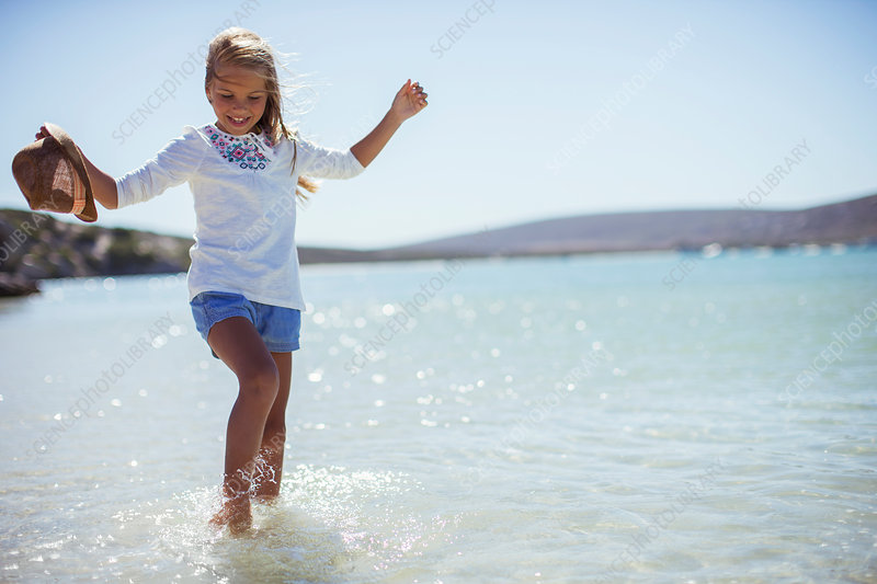 Young girl splashing in water on beach