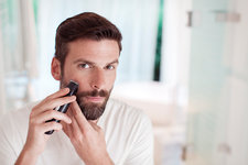 Man trimming beard in bathroom mirror