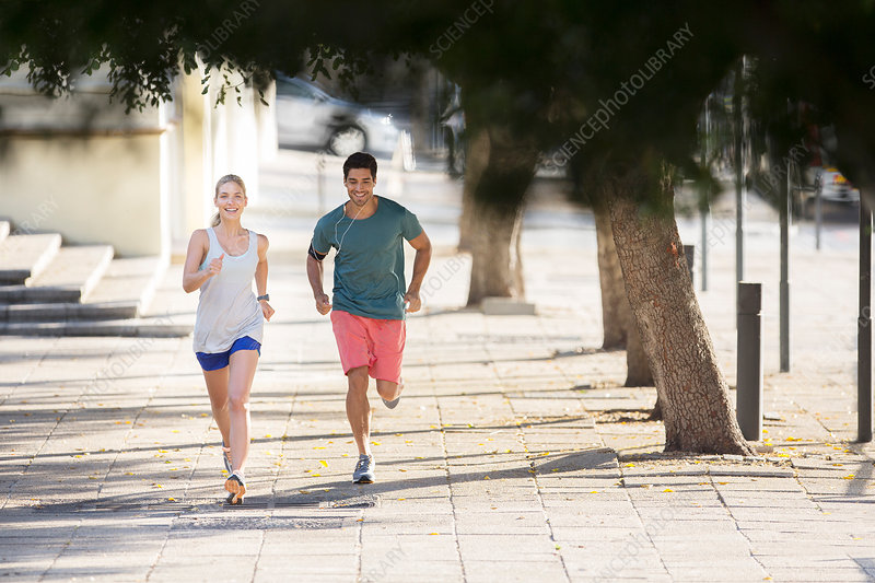 Couple running through city streets