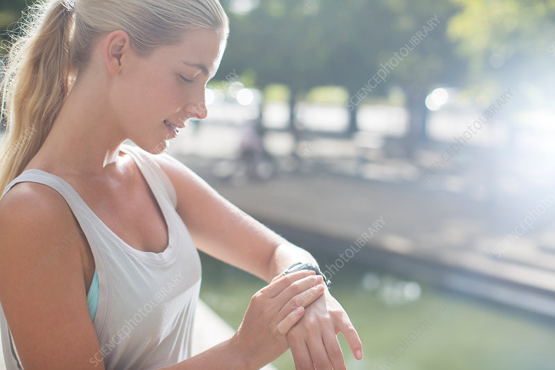 Woman looking at watch before exercising
