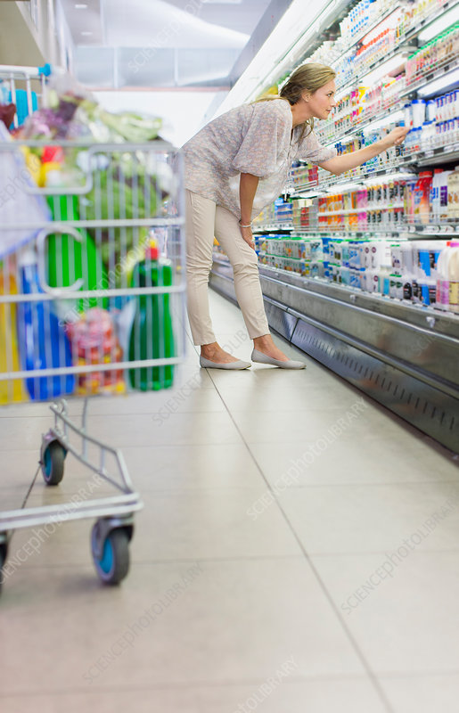 Woman examining products in grocery store