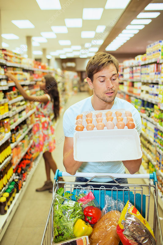 Man examining carton of eggs