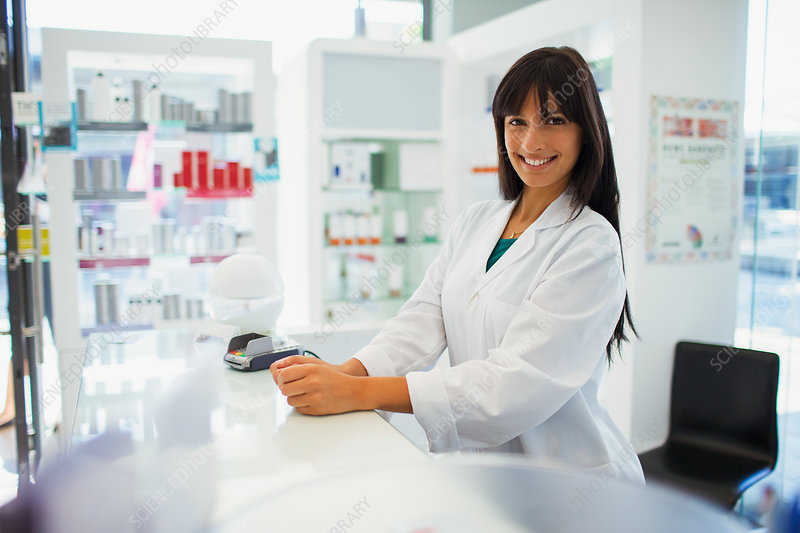 Pharmacist smiling behind counter