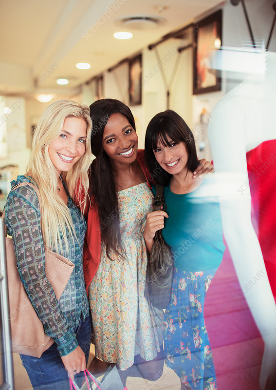 Women smiling together in clothing store