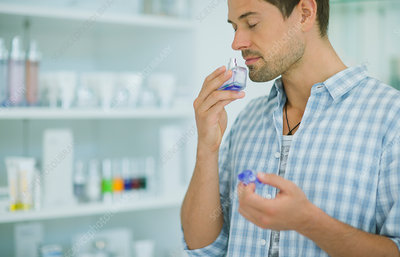 Man smelling perfume in drugstore