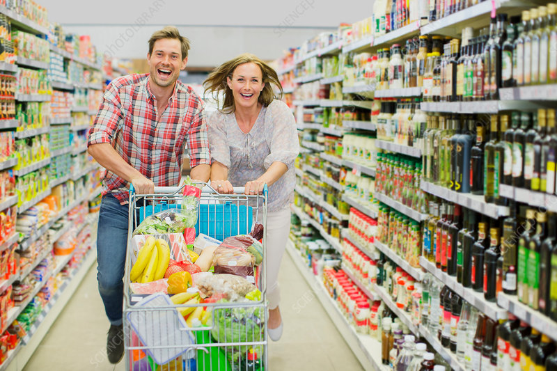 Couple playing with shopping cart aisle